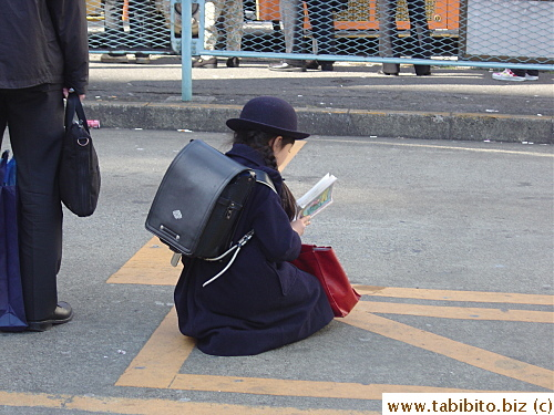 A primary school student waiting for the bus